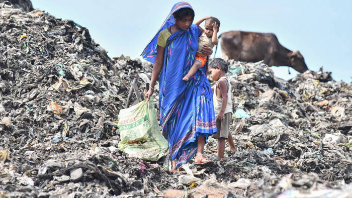 TOPSHOT - An Indian woman collects fire woods as she carries her child, at one of the largest disposal sites in north-east India, ahead of the 'World Environment Day' in Boragaon area of Guwahati on June 4, 2018. - World Environment Day is marked annually on June 5, and aims at promoting awareness and action to protect the environment. (Photo by Biju BORO / AFP) (Photo credit should read BIJU BORO/AFP/Getty Images)