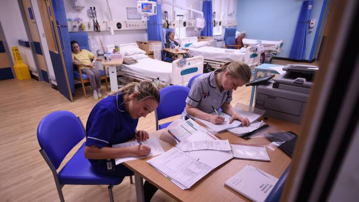 Members of clinical staff complete paperwork in the Accident and Emergency department of the 'Royal Albert Edward Infirmary' in Wigan, north west England on April 2, 2015. British Prime Minister David Cameron kicked off his re-election campaign Saturday, March 28, 2015, for May's tight poll by echoing his main rival with a new promise to improve the state-run National Health Service (NHS). Polling by Ipsos MORI indicates that the NHS, which provides across-the-board care for Britons and is mostly free, is the most important issue for voters. AFP PHOTO / OLI SCARFF (Photo credit should read OLI SCARFF/AFP/Getty Images)
