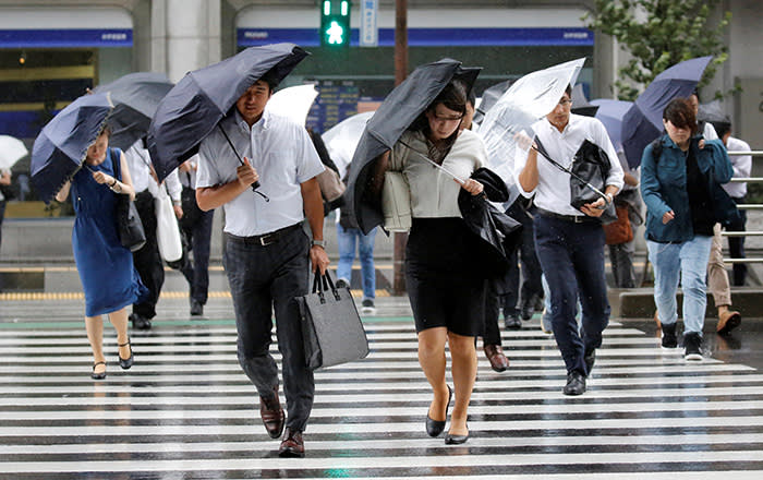 Passersby using umbrellas struggle against a heavy rain and wind as Typhoon Shanshan approaches Japan's mainland in Tokyo, Japan August 8, 2018. REUTERS/Toru Hanai