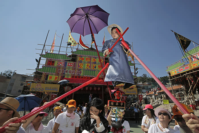 A child dressed in a traditional Chinese costume floats in the air, supported by a rig of hidden metal rods, during a parade on the outlying Cheung Chau island in Hong Kong to celebrate the Bun Festival Tuesday, May 22, 2018. Thousands of local residents and tourists flocked to an outlying island in Hong Kong to celebrate a local bun festival on Tuesday despite the recording-breaking heat. The festival features a parade with children dressed as deities floated on poles. Later on Tuesday, contestants will take part in bun-scrambling competition. They will race up a 14-meter bamboo tower to snatch as many plastics buns as possible. Buns that are higher up are worth more points. (AP Photo/Kin Cheung)