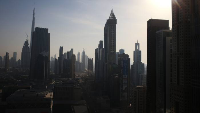 City skyscrapers and the Burj Khalifa tower, left, sit on the city skyline as the sun passes overhead in Dubai, United Arab Emirates, on Friday, Nov. 6, 2015. Home prices in the emirate dropped 12 percent in the 12 months through June, the biggest decline among 56 residential markets tracked by broker Frank Knight LLP. Photographer: Jasper Juinen/Bloomberg