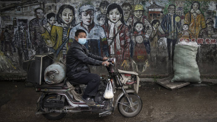 WUHAN, CHINA - APRIL 23:CHINA OUTA resident rides a bike past a graffiti wall on April 23, 2020 in Wuhan, Hubei Province, China.The government started lifting outbound travel restrictions on April 8 from Wednesday after almost 11 weeks of lockdown to stem the spread of COVID-19. (Photo by Getty Images)