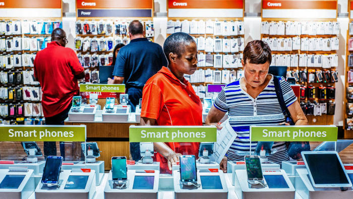 An employee assists a customer beside a display of smartphones at a mobile phone store inside the Vodacom World mall, operated by Vodacom Group Ltd., in the Midrand district of Johannesburg, South Africa, on Thursday, Feb. 2, 2017. Vodacom, which is 65 percent owned by Newbury, England-based Vodafone and the South African market leader by subscriber numbers, is expanding its internet offering to offset falling voice revenue. Photographer: Waldo Swiegers/Bloomberg
