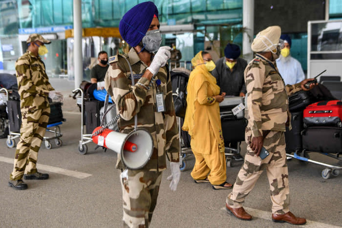 Central Industrial Security Force (CISF) personnel patrol as British nationals queueing before checking-in for a special flight to London after the government eased a nationwide lockdown imposed as a preventive measure against the COVID-19 coronavirus,at Sri Guru Ram Das Ji International Airport on the outskirts of Amritsar on May 13, 2020. (Photo by NARINDER NANU / AFP) (Photo by NARINDER NANU/AFP via Getty Images)