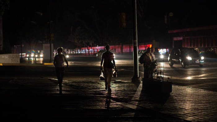 People walk along a dark street during a new power outage in Caracas, on March 30, 2019. - Venezuelan security forces fired tear gas Saturday to disperse demonstrators in Caracas outraged by massive power outages that have kept much of the country in darkness since early March. (Photo by CRISTIAN HERNANDEZ / AFP) (Photo credit should read CRISTIAN HERNANDEZ/AFP/Getty Images)