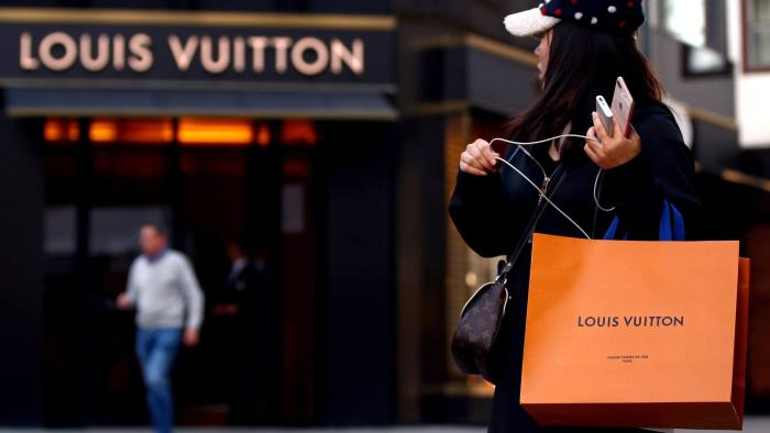 FILE PHOTO: A woman with a Louis Vuitton-branded shopping bag looks towards the entrance of a branch store by LVMH Moet Hennessy Louis Vuitton in Vienna, Austria October 4, 2018. REUTERS/Lisi Niesner/File Photo