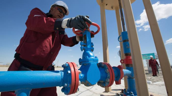 An oil worker adjusts the wheel of a flow valve on a modern oil pumping unit at an oilfield operated by Embamunaigas, a unit of KazMunaiGas Exploration Production, in Akkystau village, near Atyrau, Kazakhstan, on Saturday, July 4, 2015. The majority Muslim country is central Asia's biggest oil producer. Photographer: Andrey Rudakov/Bloomberg