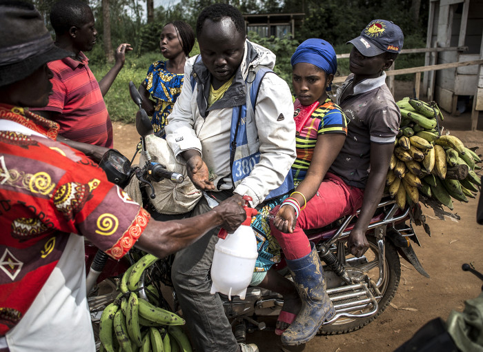 A motor taxi driver and his clients get their hands washed at an Ebola screening station before entering the city of Beni on July 13, 2019.