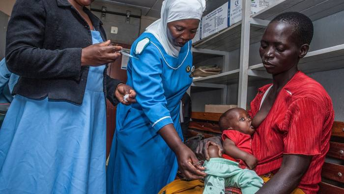 A Health Surveilance Assistant (HAS) prepares to give malaria vaccine to a child as Hanifa Likaka (C), a Senior Nursing Officer and Matron for the vaccine launch venue hospital, assists in removing a child's trousers for easy injection April 23, 2019 at Mitundu Community hospital in Malawi's capital district of Lilongwe on the first day of the Malaria vaccine implementation pilot programme in Malawi aiming to immunise 120,000 children aged two years and under to assess the effectiveness of the pilot vaccine and whether the delivery process is feasible. - Malawi spearhead today large scale pilot tests for the world's most advanced experimental malaria vaccine in a bid to prevent the disease that kills hundreds of thousands across Africa each year. After more than three decades in development and almost $1 billion in investment, the cutting-edge trial will be rolled out in Malawi's capital Lilongwe this week and then in Kenya and Ghana next week. (Photo by AMOS GUMULIRA / AFP) (Photo credit should read AMOS GUMULIRA/AFP via Getty Images)