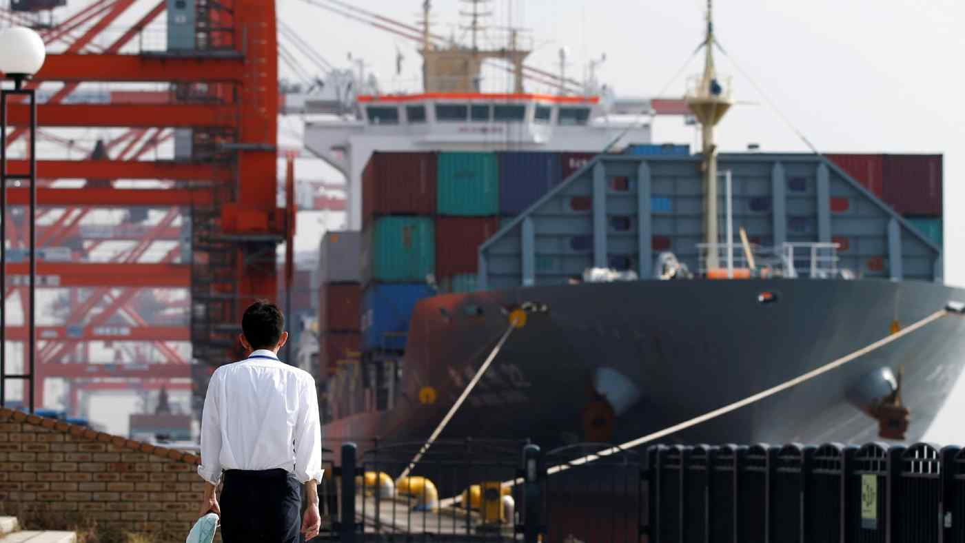 A man walks near a container ship at a Tokyo port. Many business chiefs polled by Nikkei said they had been targeted by tariffs in the U.S.-China trade war.