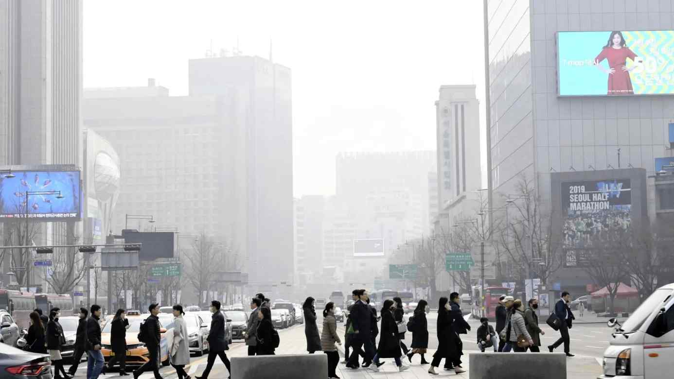 Pedestrians cross a street against a background ofsmog in Seoul on March 5.