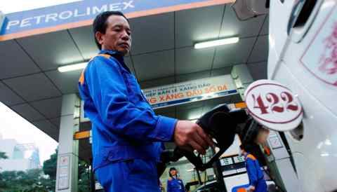 A man pumps gasolineat a gas station in Hanoi, run by Vietnam's top fuel importer and distributorPetrolimex.