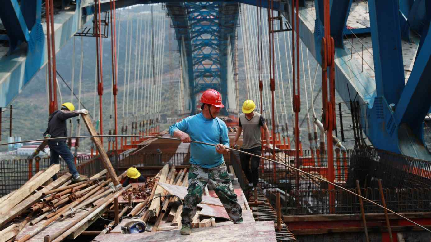 Work proceeds on a railway bridge in Guizhou Province. Chinaplans6,800 km of new rail construction this year.