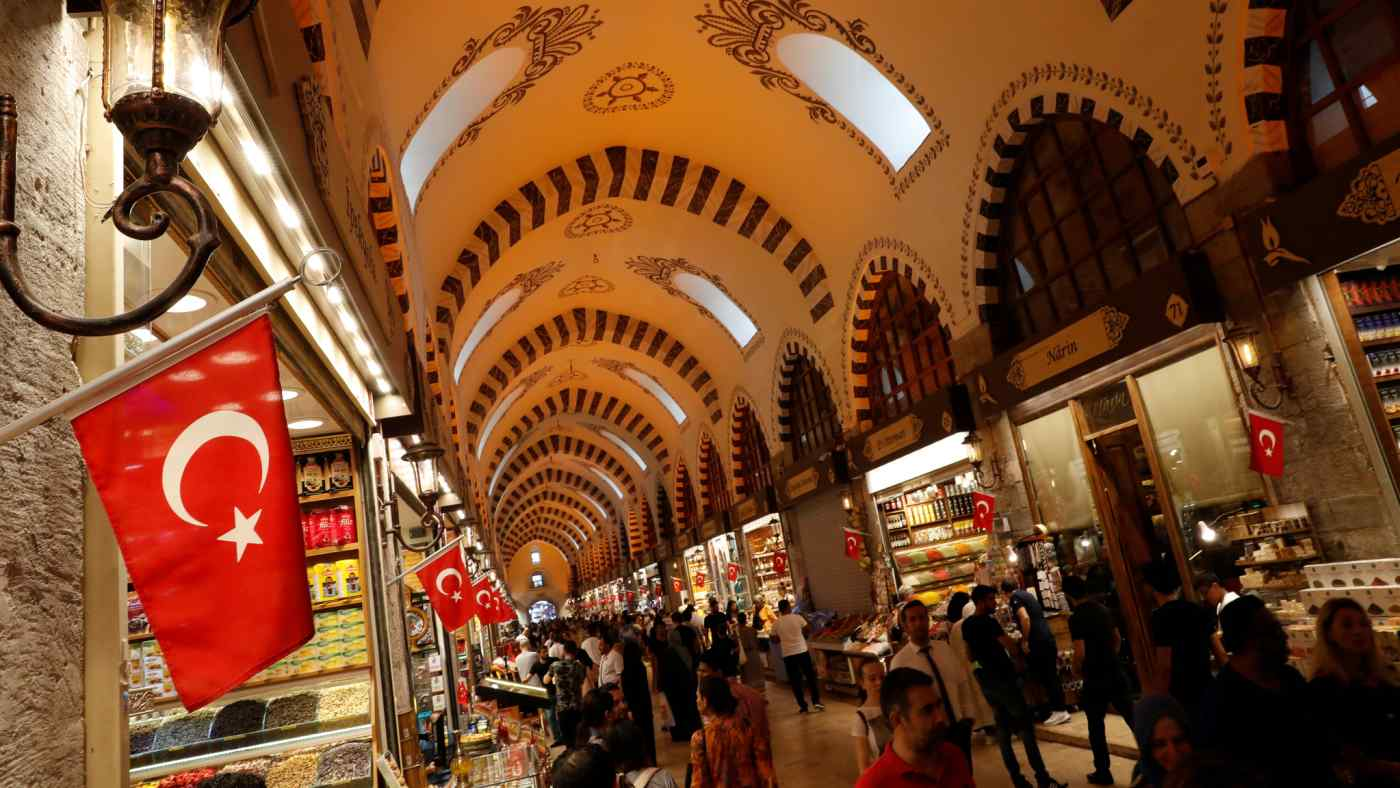 People shop at the Spice Bazaarin Istanbul. The sharp drop in the value of the local currency has prompted Toyo Ink to postpone plans to build a factory in Turkey.