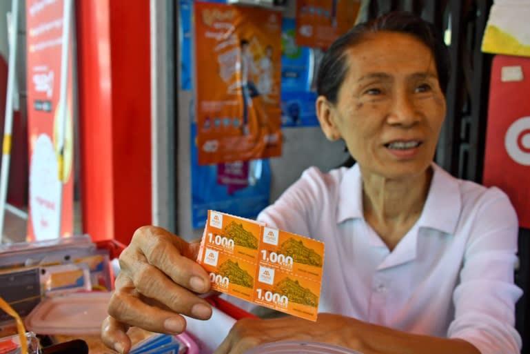 A woman sells Mytel prepaid cards at a shop in Yangon. (Photo by Yuichi Nitta)