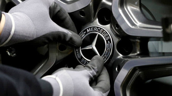 FILE PHOTO: An employee of German car manufacturer Mercedes Benz installs a hubcap at a A-class model at the production line at the Daimler factory in Rastatt, Germany, February 4, 2019. REUTERS/Kai Pfaffenbach//File Photo