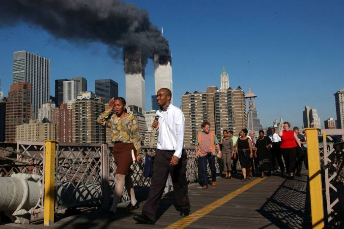 People walk over the Brooklyn Bridge as the World Trade Center burns September 11. Mr Bloomberg responded to the downturn by raising property taxes