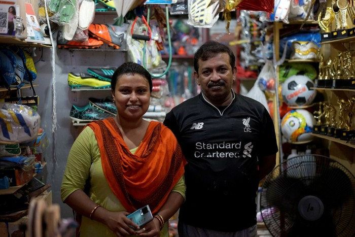 Mousumi and Arup Karmaker at their hole-in-the-wall sporting goods shop