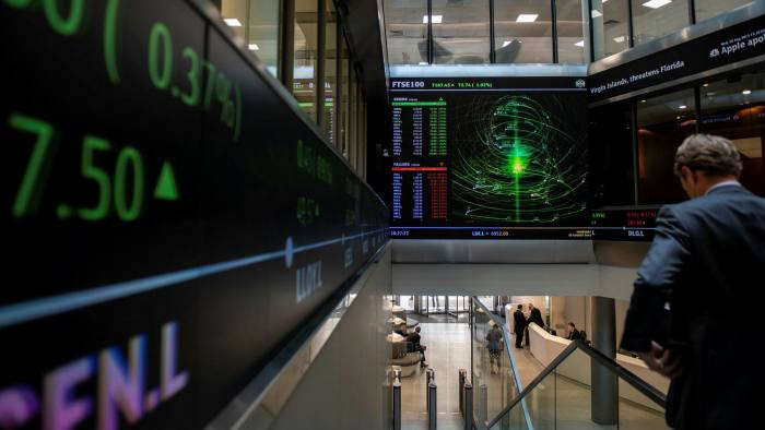 Financial market figures are shown on big screens and a ticker in the main entrance at London Stock Exchange