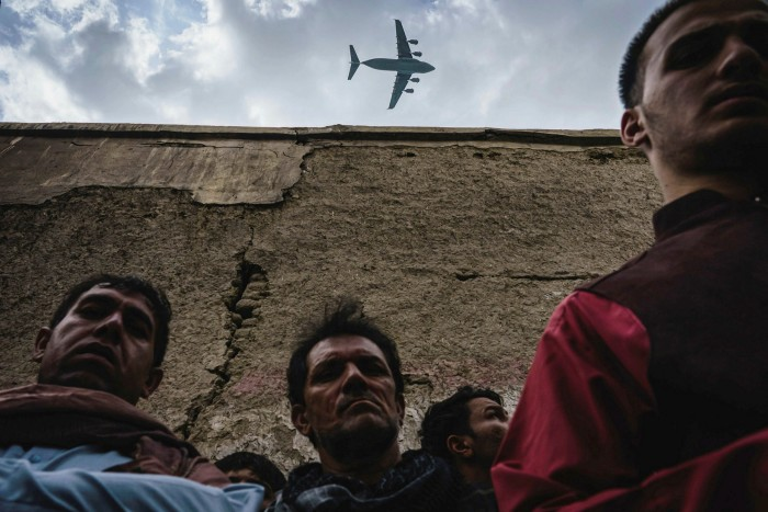 A military transport plane flies over a group of men who had gathered at the site of a US drone strike in Kabul, August 30