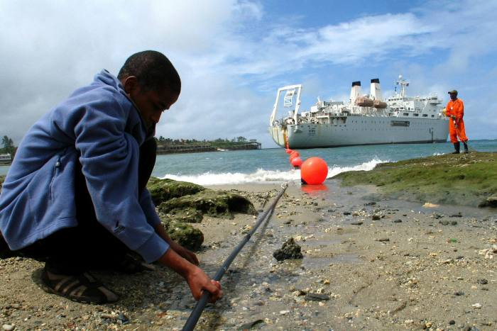 A Kenyan boy examines the Teams fiber optic cable in Mombasa, Kenya. Cable landings and data centres naturally favour coastal cities