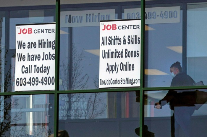 A woman walks past a job advert in New Hampshire. US economic growth in the first half of the year averaged 6.4% on an annualised basis, while employment has jumped by 3m since the start of the year