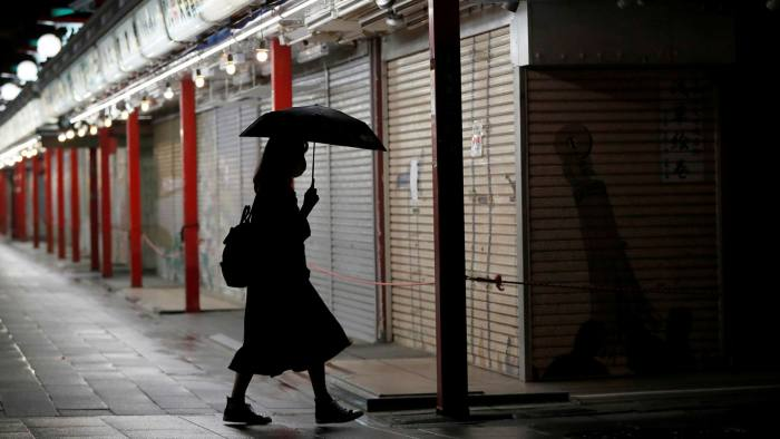 A passerby wearing a face mask walks past shuttered shops in Tokyo, Japan