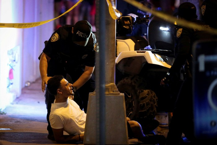 Police detain a man as they enforce an 8pm curfew imposed by local authorities in Miami Beach
