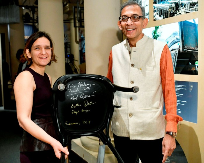 Nobel laureates in economics Abhijit Banerjee and Esther Duflo pose after signing chairs at the Nobel Museum in Stockholm in 2019