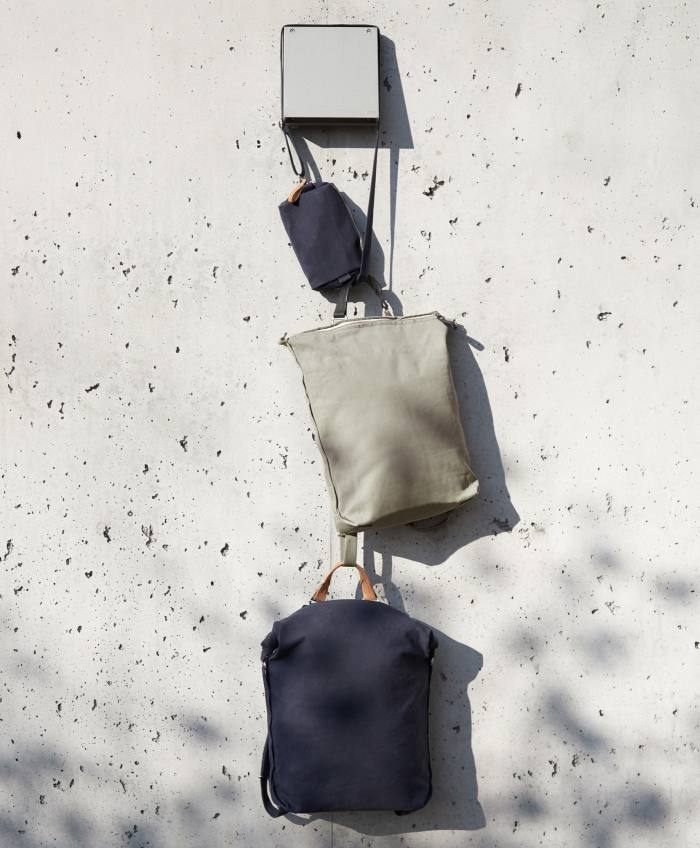 QWSTION navy hip pouch, € 70, limestone zip pack, € 275, and navy roll pack, € 295