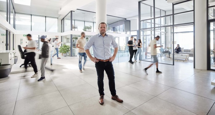 Yuri Arcurs in a large spacious workspace with people milling around behind him