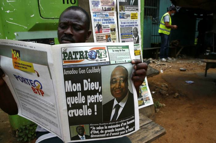 A man reads the news in Abidjan on Thursday, the day after Gon Coulibaly's death