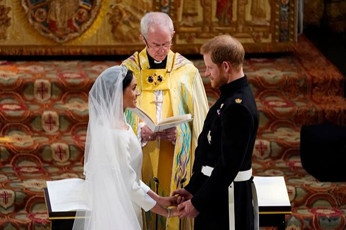 Welby standing behind Markle and Prince Harry, who are facing each other and holding hands
