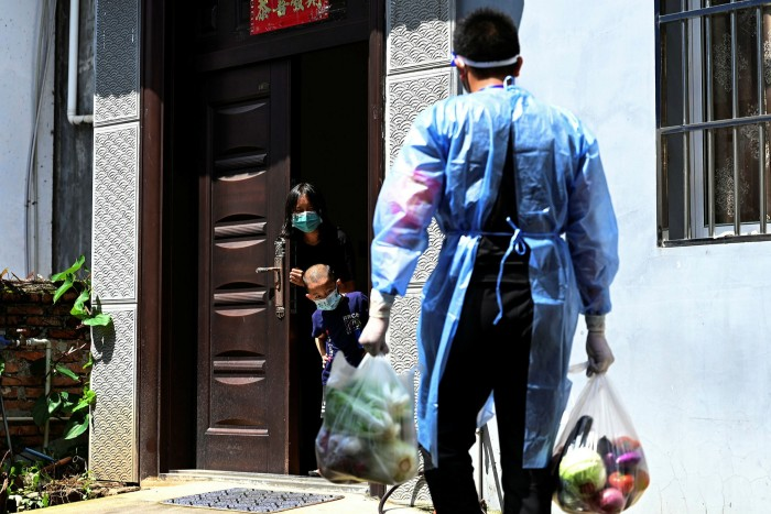 Residents watch a community worker deliver daily necessities in the city of Ruili in China's south-western Yunnan province