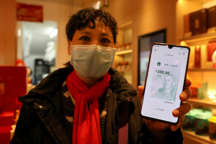 A customer shows an 'e-yuan' on her smartphone in Beijing. The digital currency is issued and regulated by China's central bank and is guaranteed by the state