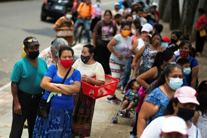 Guatemala City residents are provided ue for lunch packs provided by the government