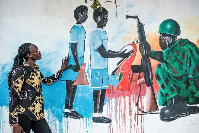 Activist Shama Peace Elia in front of a peace mural in Juba. She says 'we could have been in a good situation by now — the country would be built, would be somewhere'
