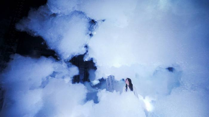 A person is hard to detect, standing among white clouds
