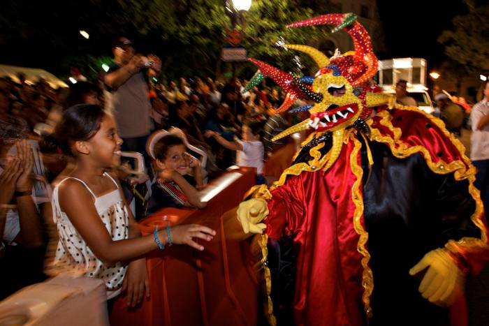 A'vejigante', or a costumed reveler, greets children in the carnival of Ponce, Puerto Rico's second city