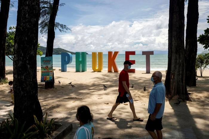 People wearing face masks on Patong Beach in Phuket, Thailand