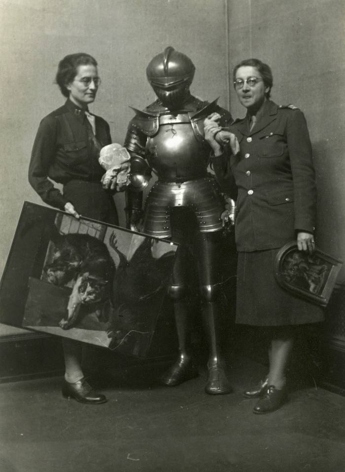 Black and white photo of two women standing on either side in armor holding paintings