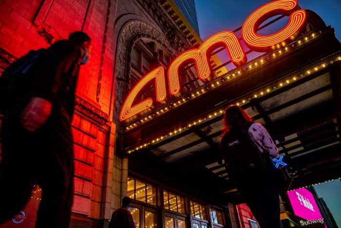 Pedestrians pass in front of an AMC movie theater at night in the Times Square neighborhood of New York