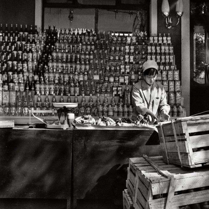 A shop girl stands in front of bottles of spirits