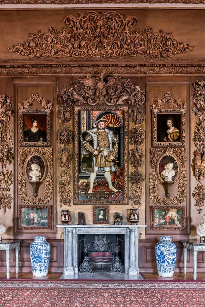 An imperious Henry VIII, in a portrait from the studio of Hans Holbein, looks down on the Carved Room