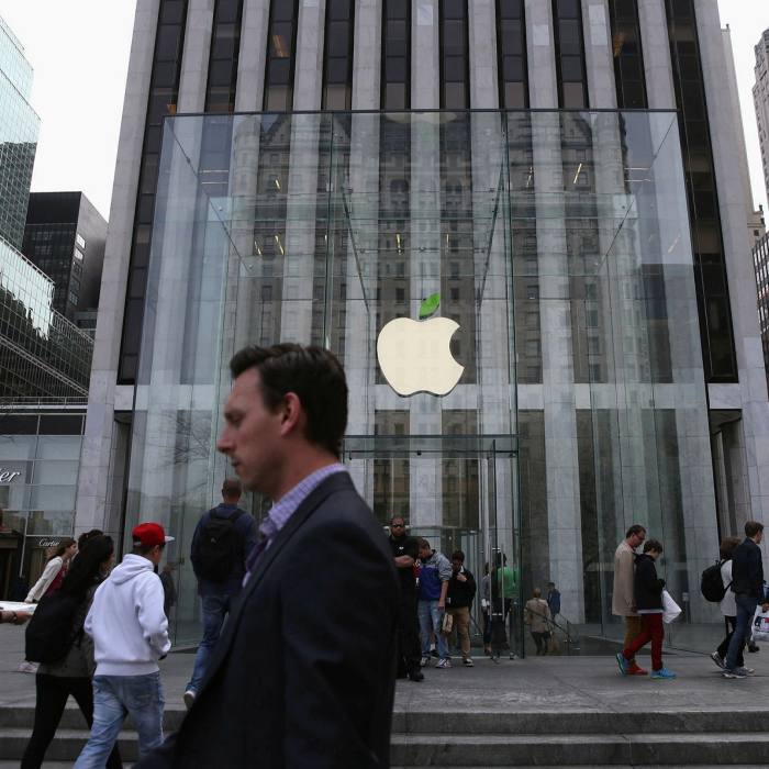 People walk past an Apple store in New York. The group plans to cut its missions by 75% by 2030 across its entire supply chain