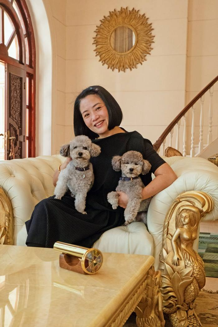 "Fashion designer Guo Pei at home in Beijing with her poodles Nuomi (""Sticky Rice"", near right) and Zhuanzhuan"