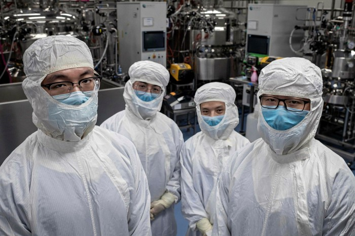 Sinovac engineers in a biotech lab in Beijing. The company has said it could complete phase two trials of a vaccine and go to production by July, according to local media