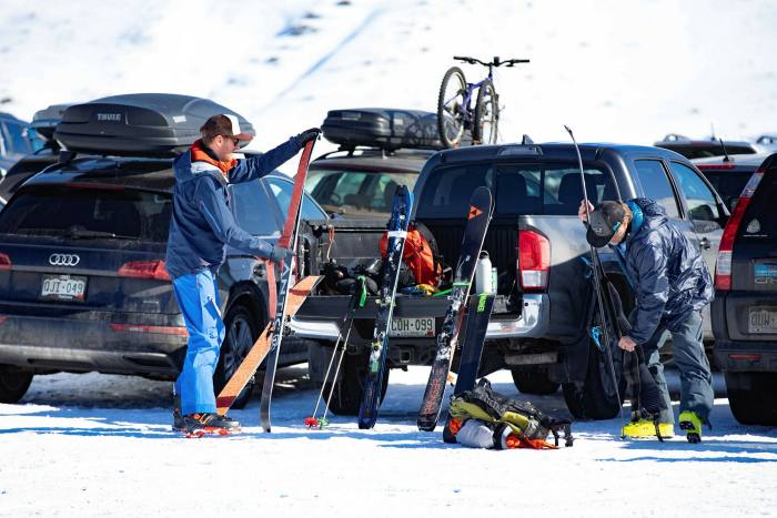 Skiers fix skins, ready to climb the mountain at Bluebird Backcountry