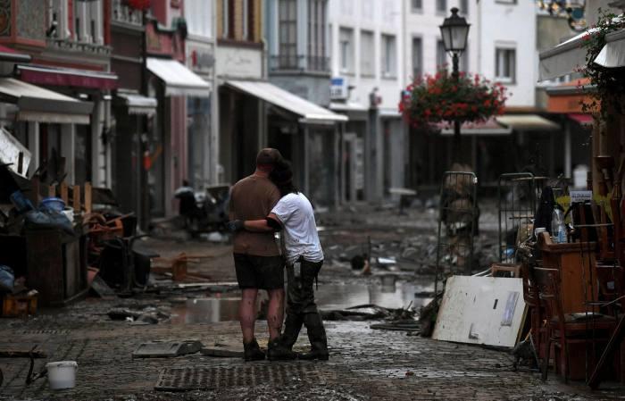 Umarmt, wenn ein Paar zwischen den Trümmern steht, die durch Hochwasser in Deutschland verursacht wurden