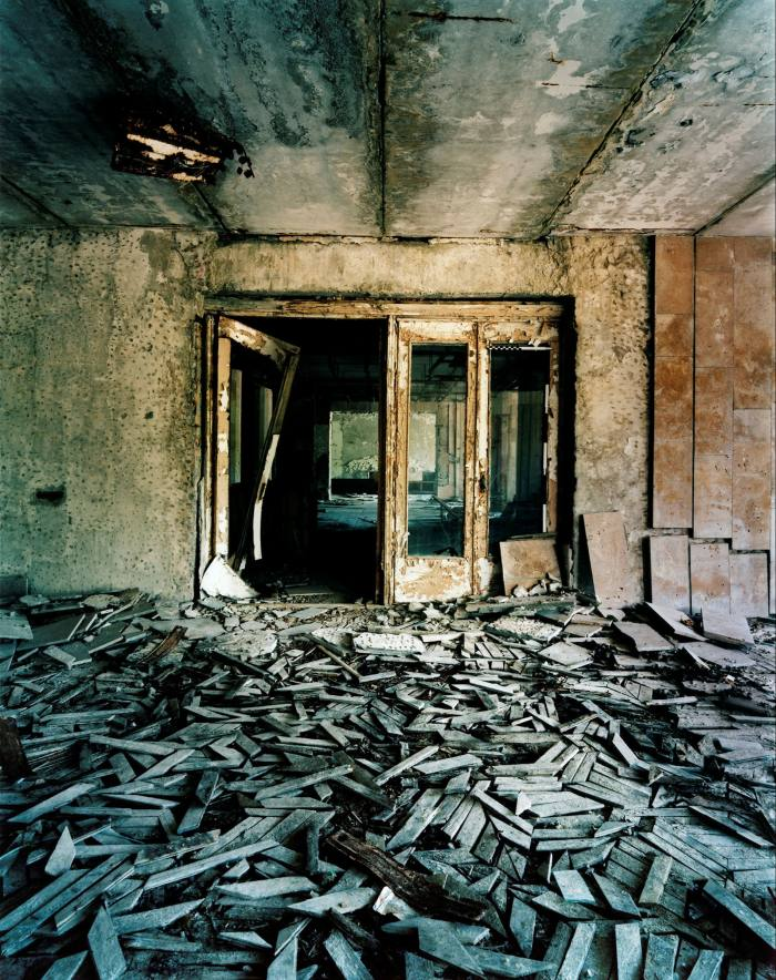 In an abandoned building, unevenly gray pieces of wooden floor are piled up in front of a rusty door
